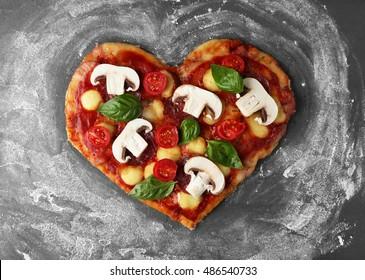 Tasty pizza in heart shape on table