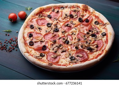 Tasty pizza on the dark wooden background