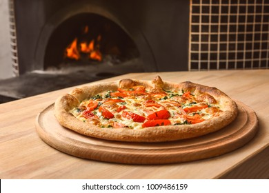 Tasty pizza on table against stove in kitchen