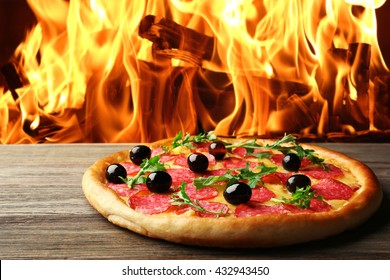 Tasty pizza with salami and olives on wooden table against fire flame background