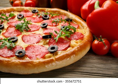 Tasty pizza with salami and red vegetables on wooden background, close up