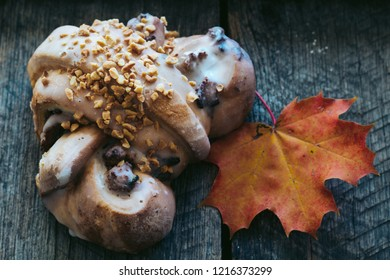 tasty polish traditional Saint Martin's croissant with nuts, almonds and white poppiescalled rogal swietomarcinski and colorful autumn leaf on wooden background