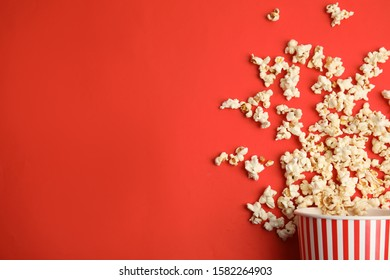 Tasty pop corn on red background, flat lay. Space for text