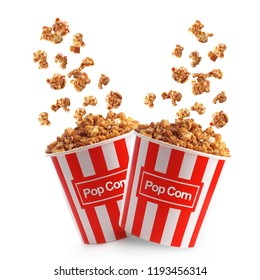 Tasty popcorn with caramel falling into cups on white background