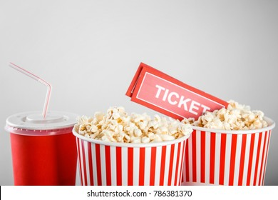Tasty popcorn, drink and tickets on light background