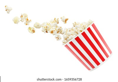 Tasty popcorn falling out of a red striped carton bucket, isolated on white background