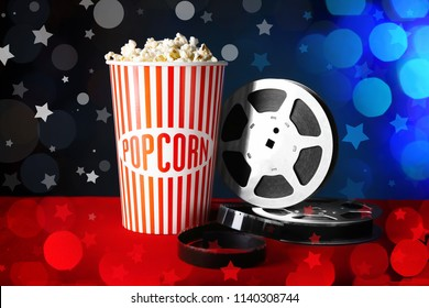 Tasty popcorn and filmstrip on table against color background. Cinema evening. Blurred lights and stars in foreground