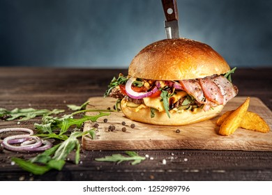 Tasty pork hamburger on dark wooden board pierced with knife, surrounded by french fries, raw meat and black pepper. Free space for text