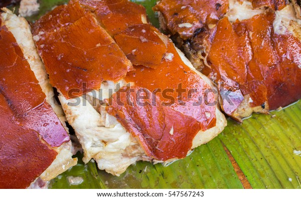 Tasty pork meat cooked on grill. Sliced pork barbecue with gold skin. Filippino dish lechon close image for restaurant menu or eatery illustration. Juicy meat ready for eat. Traditional meat cuisine
