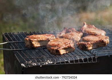Tasty pork steaks  grilling outdoor with natural BBQ smoke in sunny day