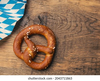 Tasty pretzel with Bavarian flag on a rustic wooden table, Oktoberfest or traditional Bavarian food concept