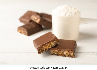 Tasty protein bars and scoop of powder on white table. Space for text