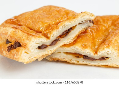 Tasty puff pastry dessert cut in half . Delicious pastries with chocolate on light background.