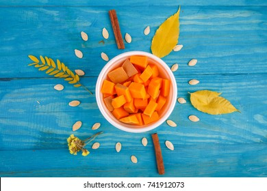 Tasty pumpkin in bowl on the blue background. Food concept.