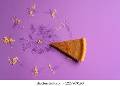 Tasty pumpkin pie slice and the visible traces of a whole pie, on a purple background. Minimalism image. Delicious holiday dessert context.
