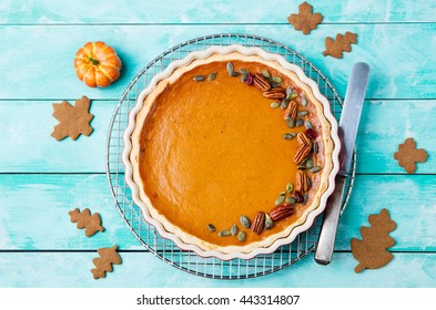 Tasty pumpkin pie, tart made for Thanksgiving day in a baking dish on a colling rack. Turquoise wooden background Top view Copy space