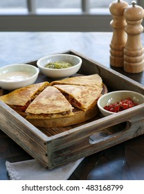 Tasty quesadilla with sauce in rustic style
