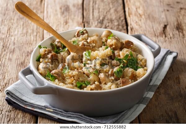 Savoureux quinoa avec champignons, persil et oignon en gros plan dans un pot sur la table. horizontal