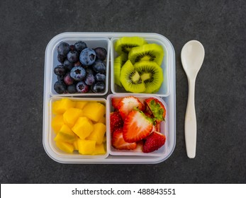 Tasty raw fruits in plastic lunch box. Bento box. Take away food. Vegetarian food.