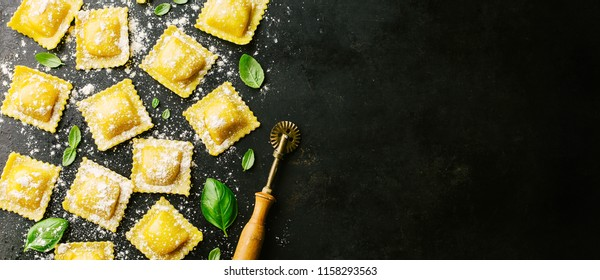Tasty raw ravioli with flour and basil on dark background. Process of making italian ravioli. Horizontal with copy space.