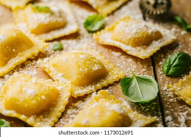 Tasty raw ravioli with flour and basil on wooden background. Process of making italian ravioli. Closeup
