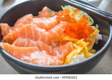 Tasty raw salmon on white cooked rice in a black bowl with black chopsticks.