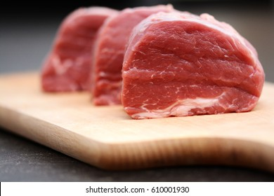 Tasty raw veal or beef meat on wooden cutting board
