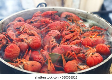 tasty red crabs are cooked on a fire with smoke in a pot outdoors