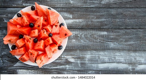 Tasty, red and juicy watermelon cut into slices. Pieces of watermelon are stacked in a plate. Still life on a wooden background. Close-up. Copy space. Horizontal.