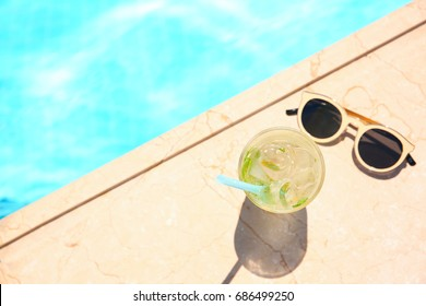 Tasty refreshing cocktail with sunglasses on edge of swimming pool