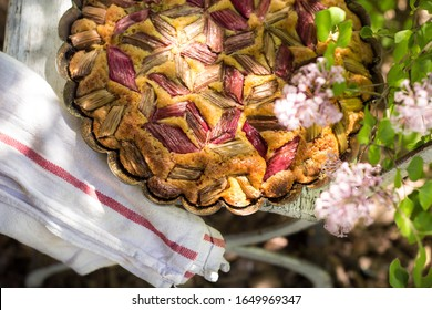 tasty rhubarb cake in the garden with lilac flowers