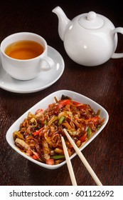 Tasty rice noodles for vegetarians with fresh ingredients as tomatoes, carrot, mushrooms, leek and celery. Green tea in beautiful white cup and pot.