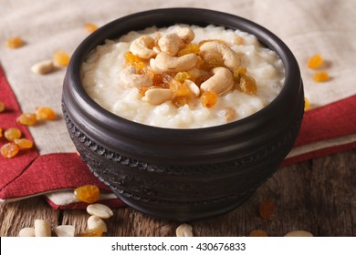 Tasty rice pudding with nuts and raisins in a bowl close-up on the table. horizontal