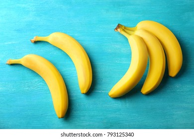 Tasty ripe bananas on color wooden background