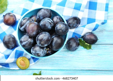 Tasty and ripe plums on blue wooden table
