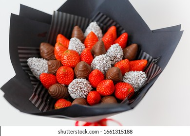 Tasty ripe strawberries in brown chocolate in the form of a bouquet on a white background. Top view
