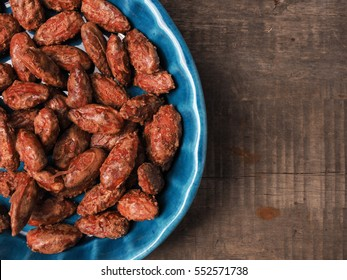 Tasty roasted almonds in a blue ceramic bowl with ingredients on wood