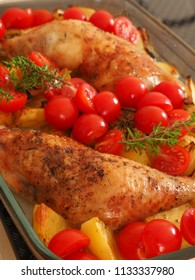 Tasty roasted chicken legs with potatoes and fresh herbs in a glass pan