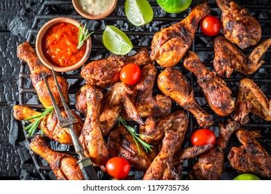 Tasty roasted chicken wings on metal grate