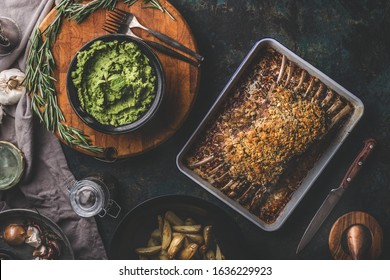 Tasty roasted lamb ribs with crust and mashed green peas with mint and  baked potatoes on dark rustic background. Top view. Meat meals. Lamb racks