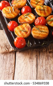 Tasty roasted new potatoes and tomatoes with rosemary closeup on a grill pan. vertical