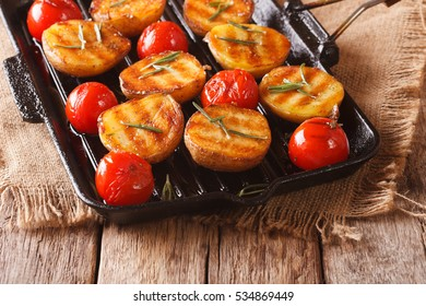 Tasty roasted new potatoes and tomatoes with rosemary closeup on a grill pan. Horizontal
