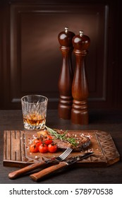 Tasty rosemary ribeye steak with cherry tomatoes on a wooden serving board. Flatware, a glass of whiskey, pepper mills. Classic recipe.
