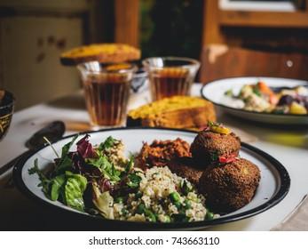 tasty rustic dinner on table, close-up. Falafels, hummus salad. Moroccan food