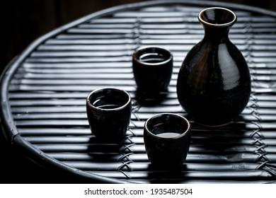 Tasty sake in black ceramics on black table. Japanese cuisine.