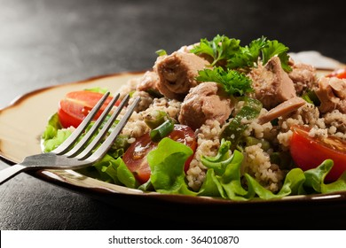 Tasty salad with couscous, tuna and vegetables on the plate