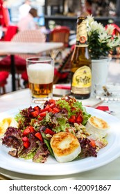 Tasty salad served on white ceramic plate with glass of beer covered with froth