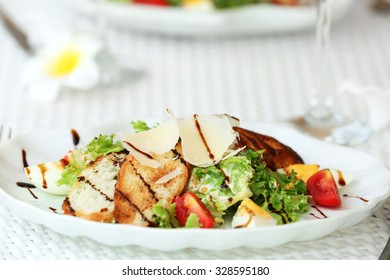 Tasty salad with wine on white served table