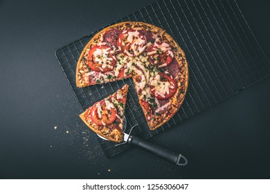 Tasty salami pizza and cooking ingredients tomatoes basil on a background. Top view