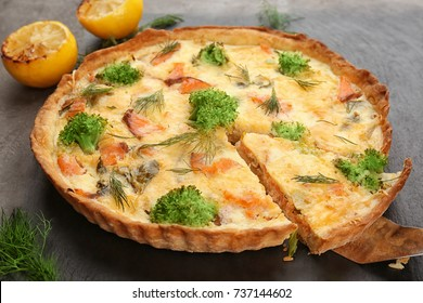 Tasty salmon quiche on table